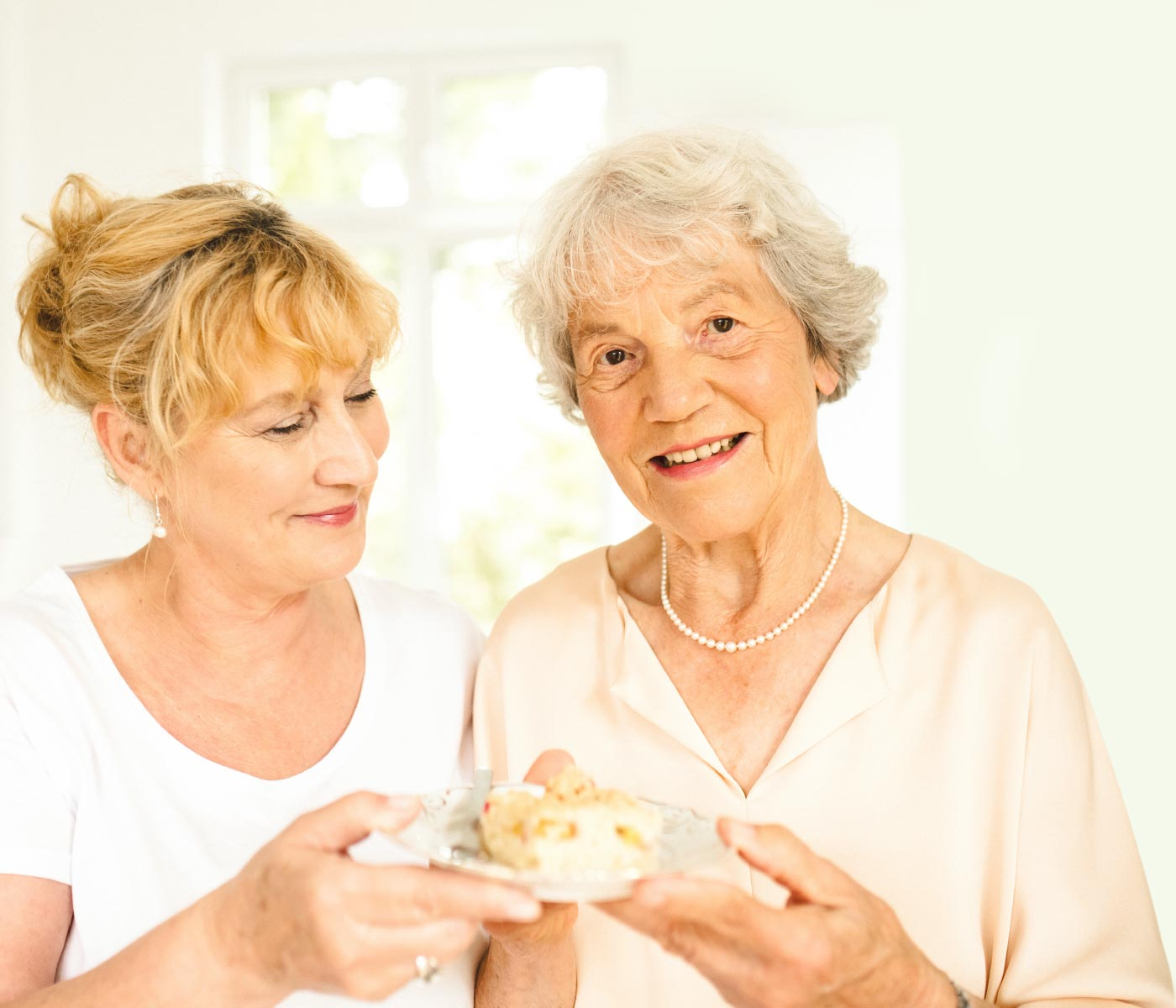 Pflegekraft reicht Seniorin ein Stück Kuchen